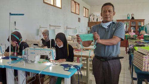 Salah satu guru SMK Yasti memperlihatkan masker buatan siswi jurusan tata busana